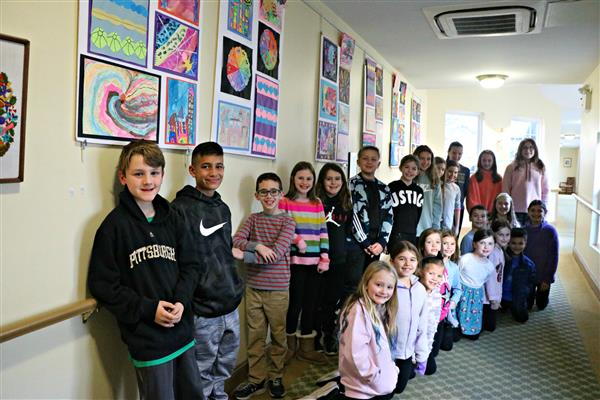 East Goshen Students pose in front of their artwork at Bellingham Retirement Community